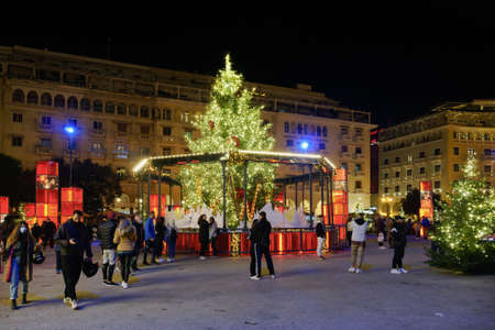 Thessaloniki, Greece - December 18 2020: Decorated Christmas tree at Aristotelous square with crowd. Night view of people around illuminated festive instalments at southern part of main city square. Editöryel