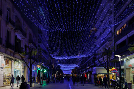 Thessaloniki, Greece - December 18 2020: Decorated Christmas LED curtain at Agias Sofias square with crowd. Night view of people around illuminated festive instalments at city pedestrian zone. Editöryel