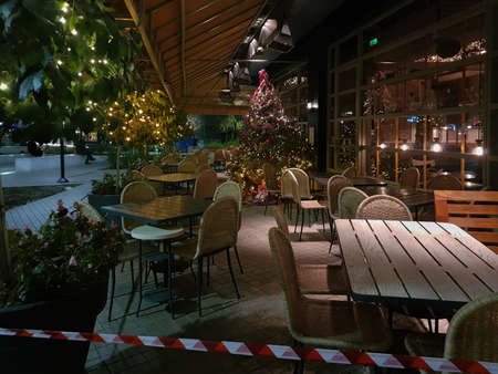 Thessaloniki, Greece - December 18 2020: Hellenic empty restaurant with Christmas decoration.Bar at night without crowd and no access ribbon at outdoor seating area closed due to covid-19 measures.