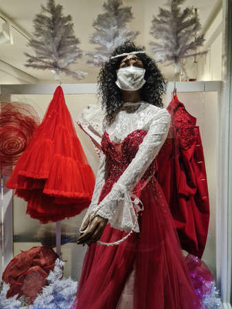 Thessaloniki, Greece - December 18 2020: Hellenic empty shop window showcase with Christmas decor. Closed due to covid-19 measures store with display dummy wearing face mask, dressed as a bride. Editöryel