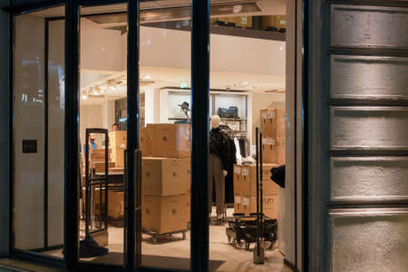 Thessaloniki, Greece - December 13 2020: Zara brand shipment boxes behind closed doors facade. Inditex Spanish retailer store entrance with stacked packages of clothes carton containers with logo.