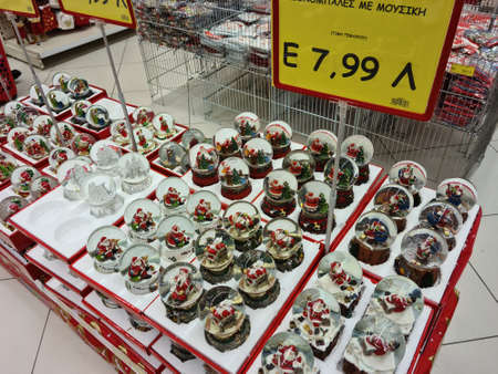 Thessaloniki, Greece - October 27 2020: Christmas snow globe balls on shelf. Festive decorations depicting Santa Claus and other figures for sale on showcase inside shop gallery, with price in euro. Editöryel