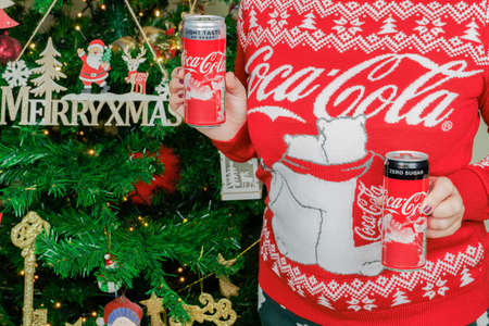 Thessaloniki, Greece - December 25 2020: Female holds Christmas Coca Cola light and zero cans with Santa Claus figure. Woman wearing sweater with logo displays seasonal beverage before decorated tree.