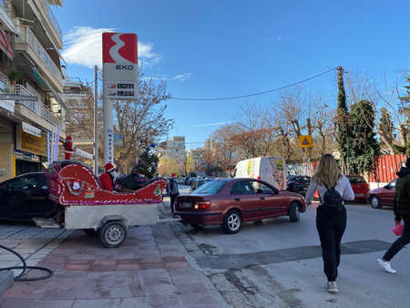 Thessaloniki, Greece - December 31 2020: Male dressed as Santa Claus sings the carols on a Sleigh. Passing car with sledge converted trailer and person with beard and red uniform of father-Christmas. Editöryel