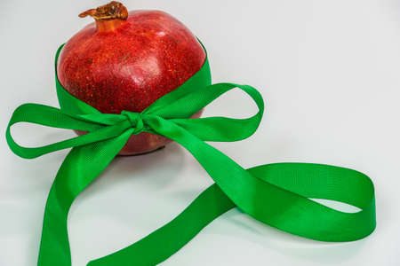 A pomegranate with a green ribbon as a new year gift against white background. Red fresh fruit with green ornamental decoration and copy space.
