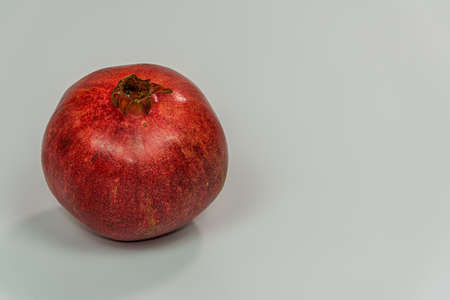 Fresh whole pomegranate against white background. Uncut red fruit closeup with copy space.