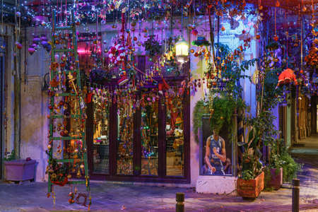 Thessaloniki, Greece - December 30 2020: Christmas decorated Hellenic shop window showcase. Illuminated night view of empty store, closed due to covid-19 measures.