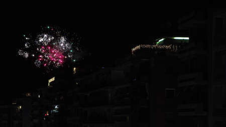 Series of fireworks above large residential area at night. New Years Eve January 01 2021 pyrotechnics at Thessaloniki, Greece for the coming of New Year.