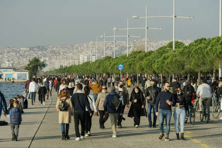 Thessaloniki, Greece - February 6 2021: Very Large number of people with covid-19 masks outdoors. Unidentified persons with face protection walk at close distance on pedestrian area of city waterfront Editöryel