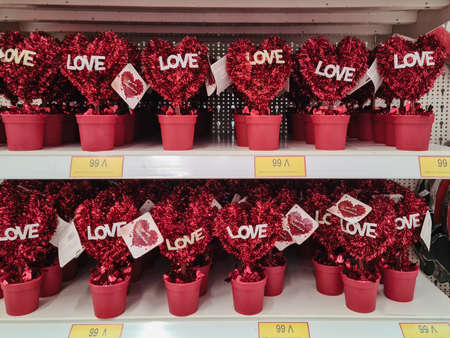 Thessaloniki, Greece - February 3 2021: Happy Valentines day plastic hearts with message on shop showcase. Interior of romantic love decor items on flower pots, sold as gifts for February 14 feast. Editöryel