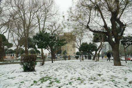Thessaloniki, Greece - February 14 2021: Medea front hits with heavy snowfall city center, with crowd moving. People in warm clothes and covid-19 masks around White Tower landmark with snow falling.