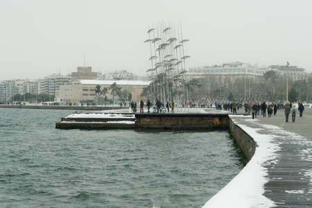 Thessaloniki, Greece - February 14 2021: Medea front hits with heavy snowfall the city center, with crowd moving. People in warm clothes and covid-19 masks at the waterfront area with snow falling.