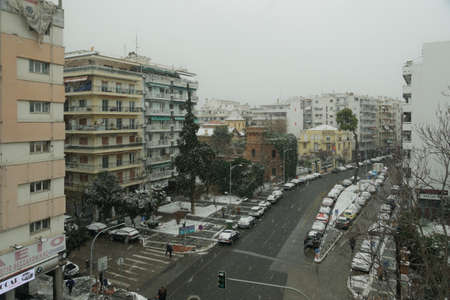 Thessaloniki, Greece - February 14 2021: Medea front hits with heavy snowfall the city center. Snow falling at Vasilissis Olgas main street with some cars moving.