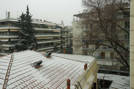 Medea front hits with heavy snowfall the city center in Thessaloniki, Greece. Snow falling on residential area with blocks of flats surrounded be trees. Stok Fotoğraf