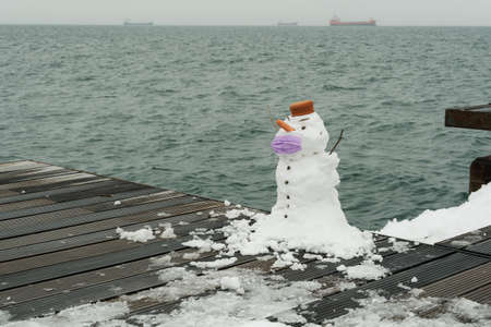 Funny snowman with face protection mask by the waterfront during the pandemic. Day view of cute white frozen construction with  mask and carrot nose against sea background.