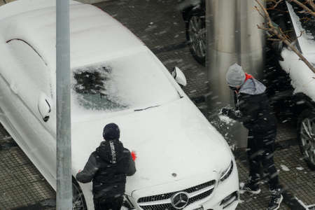 Thessaloniki, Greece - February 14 2021: Children playing during snowfall outdoors. Unidentified young males in warm clothes are having fun gathering fresh snow from a covered with ice white car. Editöryel