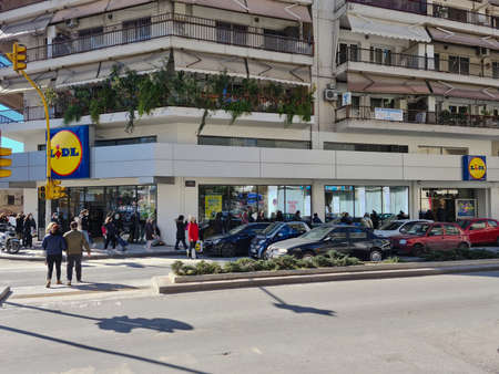 Thessaloniki, Greece February - 18 2021: Crowd with covid-19 masks queuing outside super market. Large number of people with face protection wait in line to enter LIDL Stiftung German discount store.