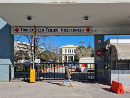 Thessaloniki, Greece - February 18 2021: Ippokrateio general hospital street entrance with sign. Day view of south gate facade of Hellenic public clinic with logo and red cross.