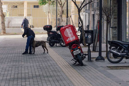 Thessaloniki, Greece - February 20 2021: Efood online delivery courier motorbike on a city road. Day view of motorcycle used to deliver take away orders contained on a red box with company logo.