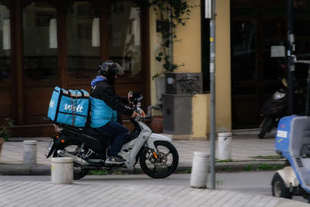 Thessaloniki, Greece - February 20 2021: Wolt food courier on motorbike speeding on city road. Day view of male with helmet riding motorcycle to deliver take away order contained on a company logo box
