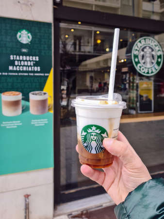 Thessaloniki, Greece – February 20 2021: Starbucks Cloud Macchiato takeaway coffee cup with a straw-less lid. Hand holding outside store a branded cold beverage with Medusa company logo. Editöryel