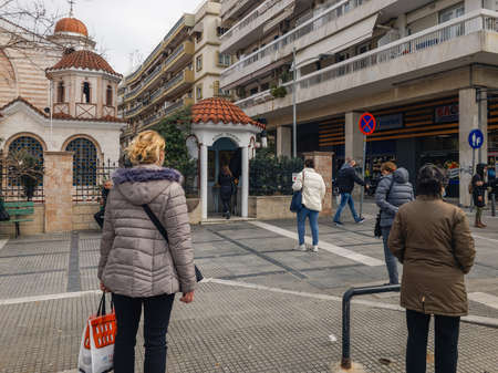 Thessaloniki, Greece March 6 2021: Crowd wearing  masks keep their distance outside a chapel. Greeks with virus masks wait to practice their religious worship outside an Orthodox church.