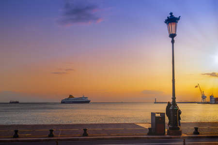 Thessaloniki, Greece - March 6 2021: Blue Star Mykonos passenger ship sailing to city seaport at sunset. Evening view of commercial boat entering calm sea harbor, with Hellenic flag waiving on a crane
