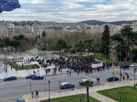 Thessaloniki, Greece - March 11 2021: Protesters holding posters moving at the city center. Day view of crowd marching at Aristotelous main square.