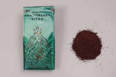 Thessaloniki, Greece - March 11 2021: Starbucks Anniversary Blend Coffee close up celebrating company 50 years. Beverage package with siren company logo next to portion of fresh ground coffee.