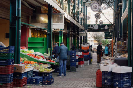 Thessaloniki, Greece - March 13 2021: People at greengrocer shop with masks. Food store with unidentified crowd wearing protective masks at enclosed market in the city center. Editöryel