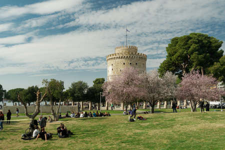 Thessaloniki, Greece March - 13 2021: Unidentified crowd on a park before the White Tower. People at the park before the city landmark on a spring day, with bloomed cherry blossom trees. Editöryel