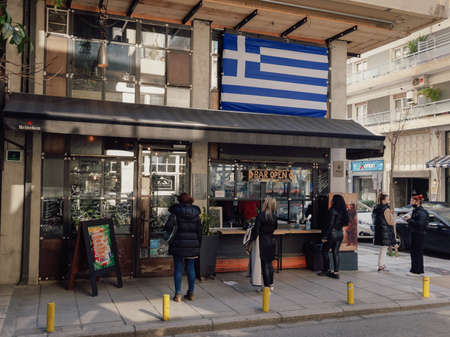 Thessaloniki, Greece - March 27 2021: Customers outside take-away working bar due to restrictions. Hellenic crowd on the pavement buy their beverage from a store with a big Greek flag above.