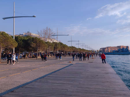 Thessaloniki, Greece - March 28 2021: Large number of people with covid-19 masks outdoors. Unidentified crowd with face protection walks at close distance on city waterfront.