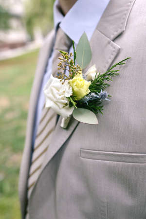 Boutonniere of white and yellow flowers with greens on lapel of a gray jacket Close-up photo