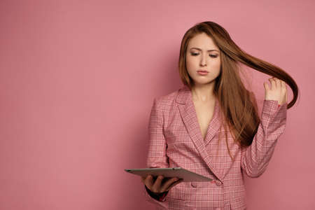 Young woman looks at the gadget surprisingly touching her hair over pink background