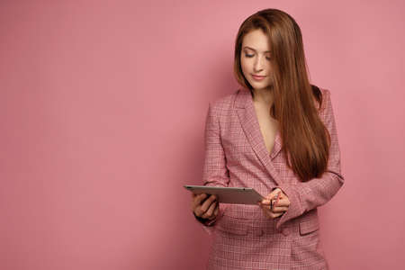Young woman looks down at the gadget over pink background Banco de Imagens