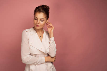 Business woman looks down thoughtfully touching her ear, pink background