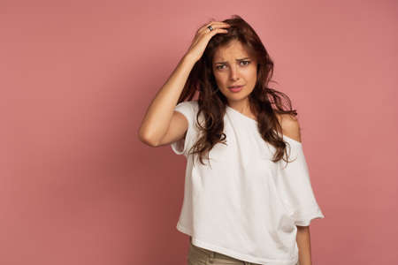 A brunette stands on a pink background in a white T-shirt and frowning holding his head with his hand. 版權商用圖片