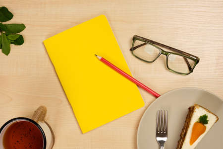 Yellow notepad with a red pencil and glasses, with a mug of tea and a piece of cake lie on a wooden table. View from above