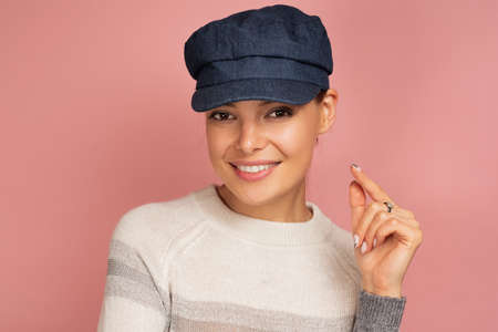 Charming girl in a blue cap and sweater openly smiles at the camera on a pink background.