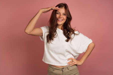 A girl in a white top is standing on a pink background smiling and putting her hand to her forehead with a visor.