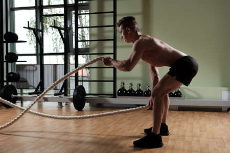 Athletic young man with battle rope doing exercise in functional