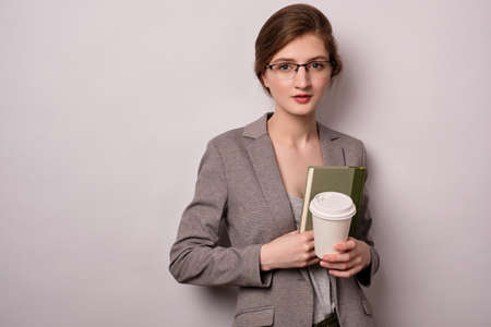 A girl in a gray jacket and glasses stands on a white background, looks at the camera and holds a plastic cup in her hands. Фото со стока - 129234104