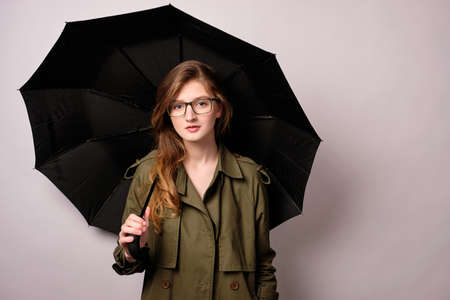 A girl in a green coat and glasses stands on a white background with a black umbrella and looks at the camera.
