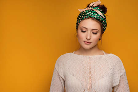 Redhead girl in a white sweater and a bright scarf on head is standing on an orange background with a relaxed face with eyes down. Фото со стока