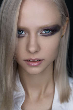 Close portrait of a platinum blue-eyed blonde with bright eye makeup in violet tones.