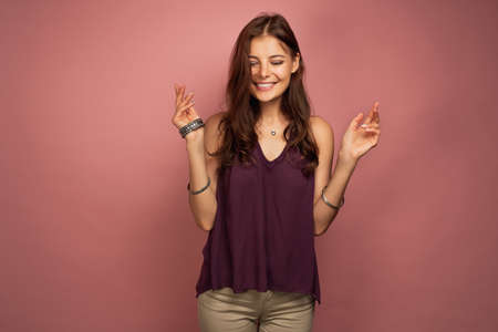 The brunette is standing on a pink background in a purple top, smiling looking down. Banco de Imagens