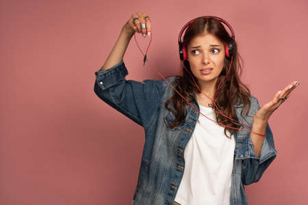 A beautiful girl in a jeans and headphones squeamishly holds the cord from them with two fingers.