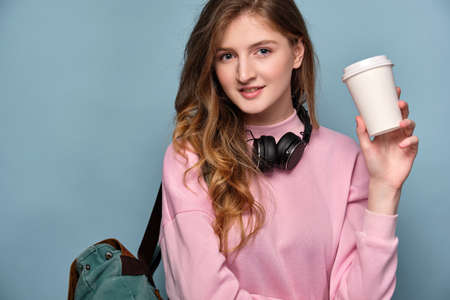 Portrait of a girl in a pink sweater and headphones with a backpack stands on a blue background with a plastic cup in his hand. Imagens