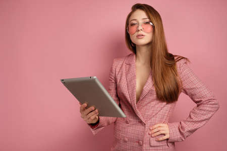 Red-haired girl in a jacket stands on a pink background with an electronic tablet and looks into the camera over glasses. Фото со стока
